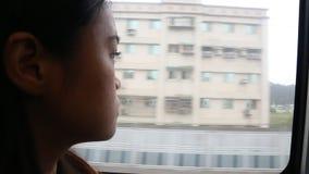 关闭坐在火车和看通过窗口的一名年轻哀伤的妇女 影视素材