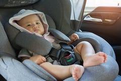 关闭坐在现代汽车座位的亚裔逗人喜爱的新出生的婴孩 库存照片