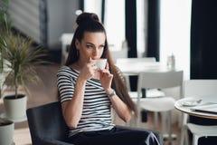关闭坐在窗口附近和品尝从一个杯子的妇女的画象一份咖啡在餐馆 免版税库存图片