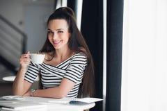 关闭坐在窗口附近和拿着一杯咖啡的妇女的画象在餐馆 免版税库存照片