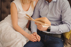 关闭坐在长沙发的甜年轻夫妇在客厅,一起读书 免版税图库摄影