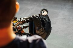 关闭坐摩托车和反射在侧视图镜子的英俊的骑自行车的人 库存图片