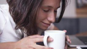 关闭坐由桌的一个华美的深色的女孩的英尺长度 女孩倾斜在杯子并且吸入芬芳 影视素材