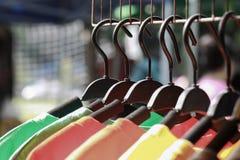 关闭垂悬五颜六色的衣裳,在挂衣架的五颜六色的T恤杉或在挂衣架的时装 免版税库存图片