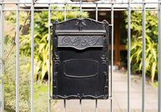 关闭垂悬在栏杆的黑金属岗位箱子 免版税库存照片
