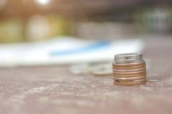 关闭堆与被弄脏的笔记本、铅笔和堆的银色泰国硬币在一张木桌上的硬币与bokeh 库存图片