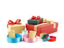 关闭堆与金纸标签皮带的五颜六色的卷丝带和有在白色隔绝的丝带弓的多色的礼物盒 库存照片
