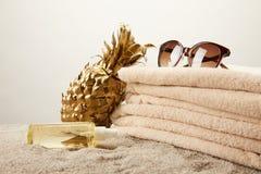 关闭堆看法毛巾、太阳镜、晒黑的油和金黄装饰菠萝在沙子在灰色背景 免版税库存照片