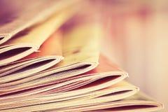 关闭堆积与模糊的bookshe的五颜六色的杂志边缘 免版税库存图片