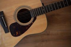 关闭声学吉他射击在木桌上的 库存照片
