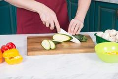 关闭夏南瓜切开了在木切板的人手有白色刀子的 蒸的菜和夏南瓜切片 库存图片