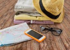 关闭夏天衣裳和旅行地图在地板上 免版税库存图片