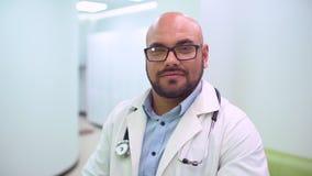 关闭外科医生或医生耳机的画象准备好在医院或诊所的操作 外科医生微笑保险柜和 股票录像