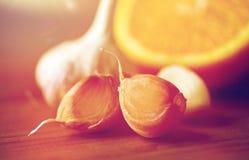 关闭大蒜和桔子在木桌上 库存照片