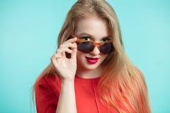关闭太阳镜的微笑反对蓝色背景的时髦的少妇射击  与拷贝空间的美好的女性模型 库存照片