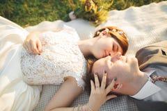 关闭夫妇画象反对河和绿色树 亲吻英俊的人的美丽的少妇户外 库存图片