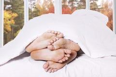 关闭夫妇脚在床上 免版税库存照片