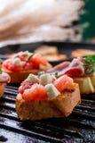 关闭套在黑格栅背景的bruschetta 鲜美开胃小菜 免版税库存图片