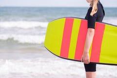 关闭女孩由举行Bodyboard的保温潜水服的海 免版税库存照片