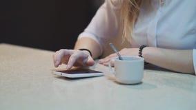 关闭女孩的手有手机的在与咖啡的咖啡馆在桌上的 股票录像