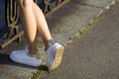 关闭女孩的美好的微小的腿站立在具体pavemen的白色运动鞋的在老铁篱芭等待的索马里兰 免版税库存图片