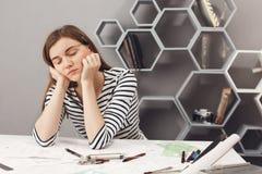 关闭女孩睡着在工作地点在期间困迷人的年轻欧洲自由职业者的工程师的画象  库存图片