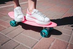 关闭女孩` s腿和脚佩带白色运动鞋 女孩是桃红色冰鞋的替换者与两只脚 有晴朗的 免版税库存照片