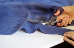 关闭女性手照片有切开紫罗兰色织品的剪刀的 库存照片