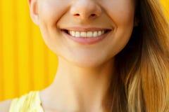 关闭妇女在黄色背景的` s微笑 免版税库存图片