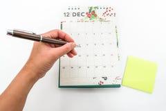 关闭妇女手在12月日历的笔记任命 库存照片