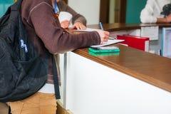 关闭妇女手文字或签字在诊所招待会区域的一个文件  选择聚焦 库存照片