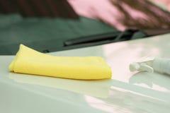 关闭妇女手清洁汽车由微纤维布料 图库摄影