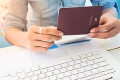关闭妇女拿着在工作sp的` s手的图象护照书 免版税库存图片