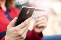 关闭妇女拿着机动性和信用卡支票帐户余额的` s手射击,使用互联网连接 人们和技术 免版税库存图片
