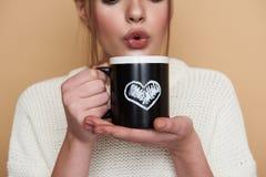 关闭妇女推出的嘴唇和吹在热的茶 免版税库存照片