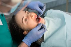关闭妇女有牙齿检查在牙齿诊所 牙医有牙齿工具的审查的患者` s牙 免版税库存照片