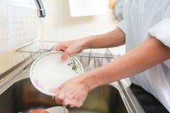 关闭妇女洗涤的盘的手在厨房里 库存照片