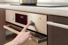 关闭妇女烹调在烤箱的手设置方式 免版税图库摄影