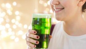 关闭妇女用在玻璃的绿色啤酒 免版税库存照片