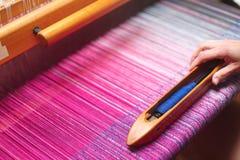 关闭妇女的手在织布机的编织的紫色和白色样式 库存图片