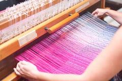关闭妇女的手在织布机的编织的紫色和白色样式 图库摄影