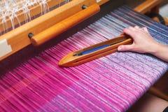 关闭妇女的手在织布机的编织的紫色和白色样式 免版税库存照片