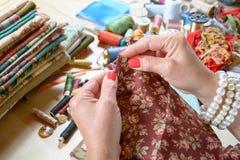 关闭妇女的手缝合的补缀品 免版税库存照片