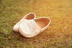关闭妇女的白色鞋子在绿草地板上 免版税库存图片