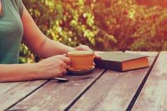关闭妇女阅读书的图象户外,在木桌和coffe杯子旁边在下午 被过滤的图象 被过滤的图象 图库摄影