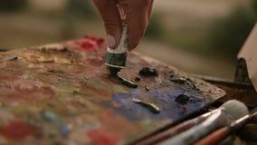 关闭妇女` s手艺术家从在调色板的管紧压油漆 为书刊上的图片做准备户外 影视素材