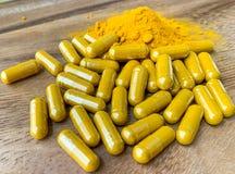 关闭姜黄或姜黄素胶囊和粉末在一张棕色木桌上 免版税库存图片