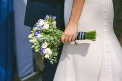 关闭婚礼花束在美丽的新娘的手上白色婚礼礼服的 库存图片