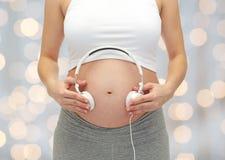 关闭孕妇和耳机在肚子 免版税库存图片