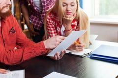 关闭学生看与Sitting At Desk,青年人老师教授的高中小组纸张文件 免版税库存照片